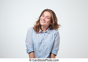 Happy cheerful young woman in blue shirt laughing on funny joke.