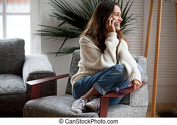 Happy cheerful young woman talking on the phone at home