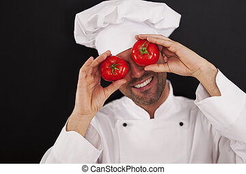 Happy chef covering his eyes of tomatoes