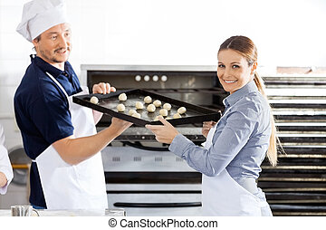 Happy Chef Giving Baking Sheet To Colleague In Kitchen