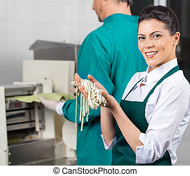 Happy Chef Holding Fresh Spaghetti Pasta In Kitchen