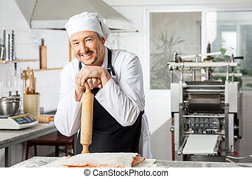 Happy Chef Holding Rolling Pin At Counter In Kitchen