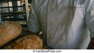 Happy chef holding tray of baked buns 4k - Portrait of happy...