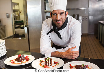 Happy chef looking at camera behind counter of desserts in a...