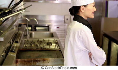 Happy chef smiling at camera beside the stove in commercial ...