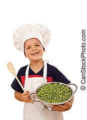Happy kid with chef hat, wooden spoon and lots of fresh green peas - isolated