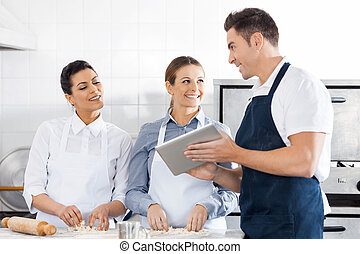 Happy Chefs Discussing Recipe On Digital Tablet In Kitchen