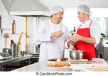 Happy Chefs Discussing While Preparing Ravioli Pasta At Counter