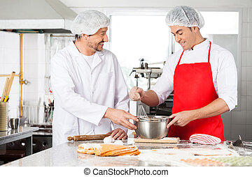 Happy Chefs Discussing While Preparing Ravioli Pasta In Kitchen