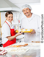 Happy Chefs Holding Pasta Tray In Kitchen