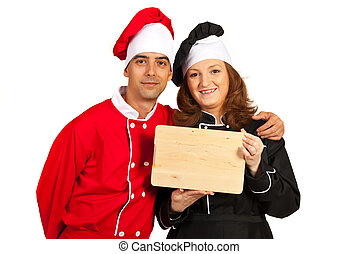 Happy chefs holding wooden board