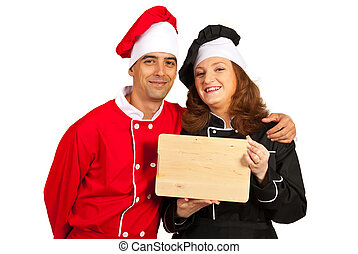 Happy chefs holding wooden cutting board