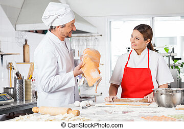 Happy Chefs Preparing Pasta At Kitchen Counter