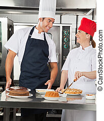 Happy Chefs Preparing Sweet Dishes in Kitchen