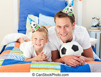 Happy child and his father playing with a soccer ball lying...