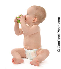 child baby boy sitting in diaper and eating green apple