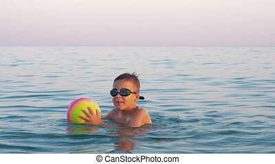 Happy child bathing in the sea with ball