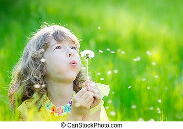 Happy child blowing dandelion flower outdoors