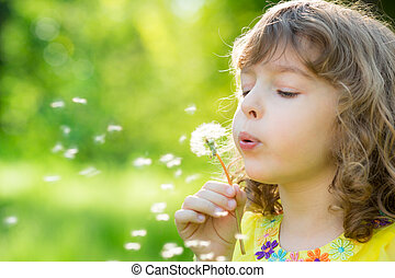 Happy child blowing dandelion flower outdoors