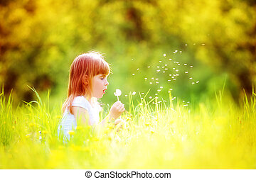 Happy child blowing dandelion outdoors in spring park
