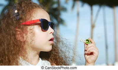Happy child blowing soap bubbles in park. Slow motion. Stock footage.