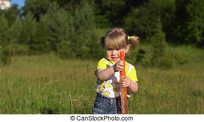 Happy child blowing soap bubbles in summer park. Slow motion