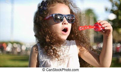 Happy child blowing soap bubbles in the park. Beautiful curly hair little girl in red glasses blowing soap bubbles. Close-up Slow shooting. Video material.