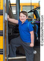 Happy child boarding school bus going back to school