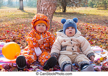 Happy child boy and girl playing with leaves in autumn park. The concept of childhood and fall.