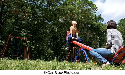 Happy Child Boy and his Mother Swinging on a Street Counterweight Swing at Playground in Slow Motion