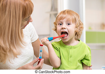 Happy child boy brushing teeth near mirror in bathroom. His mother monitoring accuracy and time of cleaning action with hourglass.