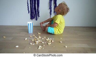 Happy child boy eating popcorn sitting on wooden floor. Gimbal motion