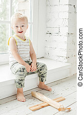 Happy child boy having fun with wooden plane toy at home