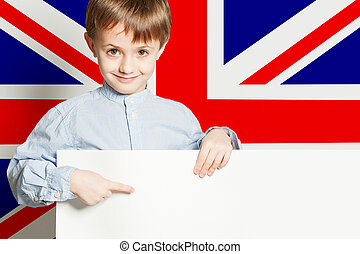 Happy child boy holding white empty paper board banner against the UK flag background