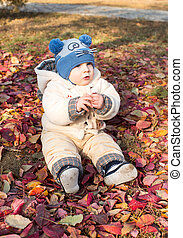 Happy child boy is playing with leaves in autumn park. The concept of childhood and fall.