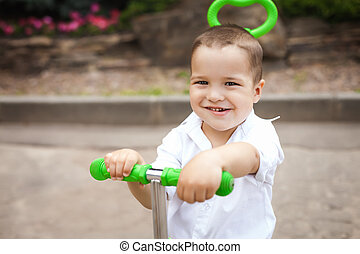 happy child boy on a trike in the park