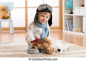 Happy child boy playing with wooden toy airplane and teddy bear in children room
