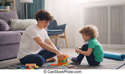 Happy child boy playing with wooden toys while mother is...