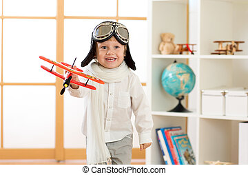 happy child boy plays with toy airplane and dreams of becoming pilot