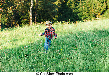 Happy child boy running on meadow in summer