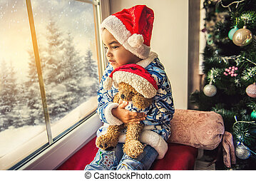 happy child boy sitting on the window waiting for Christmas