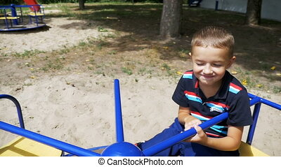 Happy Child Boy Spinning on the Carousel at the Playground in Slow Motion