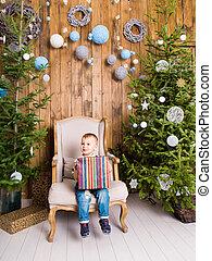 happy child boy with gift box near Christmas tree.