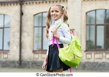 Happy child carry school bag in formal fashion uniform outdoors, back to school.