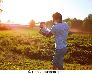 Happy child, dad and son having fun, holding on hands on a sunse