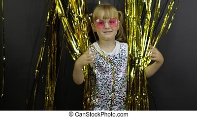 Happy child dancing, playing, fooling around in shiny foil fringe golden curtain. Little blonde kid