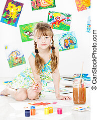 Happy child drawing with brush in album . Creativity concept.