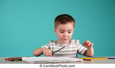Happy child drawing with pencils in album, isolated on blue....