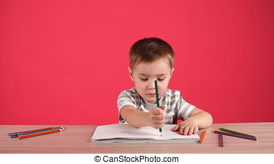 Happy child drawing with pencils in album, isolated on pink....