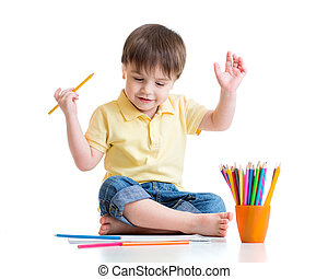 Happy child drawing with pencils in album